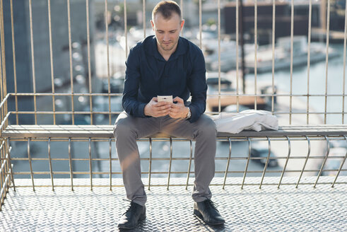 Businessman sitting on bench in front of harbour text messaging - SKCF000141