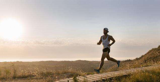 Spain, Aviles, athlete man running along a coastal path at sunset - MGOF002120