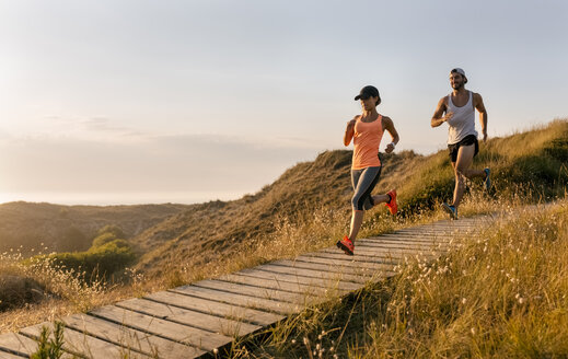 Spain, Aviles, athletes couple running along a coastal path at sunset - MGOF002123