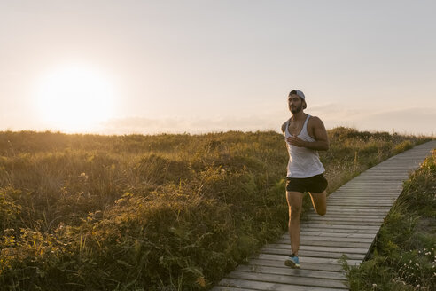 Spain, Aviles, athlete man running along a coastal path at sunset - MGOF002126