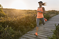 Spain, Aviles, young athlete woman running along a coastal path at sunset - MGOF002129
