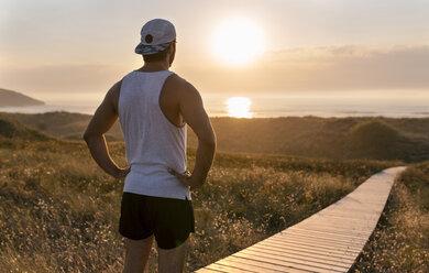 Spain, Avilés, athlete man enjoying the sunset on the beach - MGOF002135