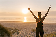 Spain, Aviles, young athlete woman enjoying the sunset on the beach - MGOF002141