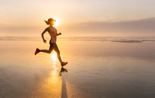 Woman running on the beach at sunset - MGOF002144