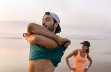 Athletes couple training on the beach in the evening, man undressing t-shirt - MGOF002147
