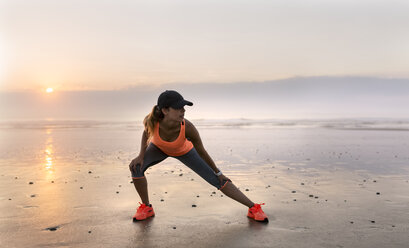 Young athlete woman doing stretching on the beach at sunset - MGOF002153