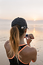 Young athlete woman looking the smartwatch on the beach at sunset - MGOF002156