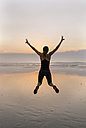 Young athlete woman jumping on the beach at sunset - MGOF002159