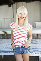 Portrait of smiling blond woman wearing striped t-shirt and Hot Pants - GDF001085