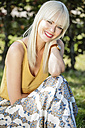 Portrait of smiling blond woman sitting on a meadow - GDF001088