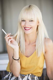 Portrait of smiling blond woman smoking cigarette - GDF001094