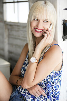 Portrait of smiling blond woman telephoning with cell phone - GDF001097