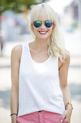 Portrait of smiling blond woman wearing mirrored sunglasses - GDF001100
