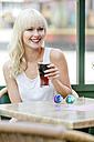 Portrait of smiling blond woman sitting at sidewalk cafe drinking cola - GDF001103