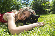 Smiling little girl lying on meadow with black cat - SARF002847