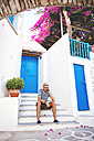 Greece, Amorgos island, young man sitting in on a step, talking on cell phone - GEMF000945