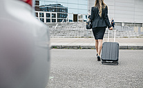 Businesswoman with suitcase on the move - DAPF000205