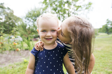 Girl kissing her little sister in the garden - HAPF000687