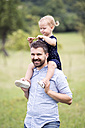 Happy father carrying little daughter on shoulders in nature - HAPF000699