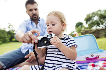 Father showing his little daughter how to use camera - HAPF000702
