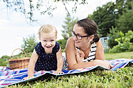 Mother and little daughter together on blanket in a park - HAPF000708