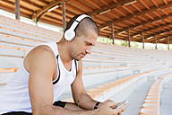 Young sportsman with headphones and smartphone - FMOF000072