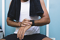 Close-up of athlete with smartwatch outdoors - FMOF000078
