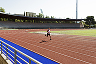 Young sportsman running on tartan track - FMOF000090