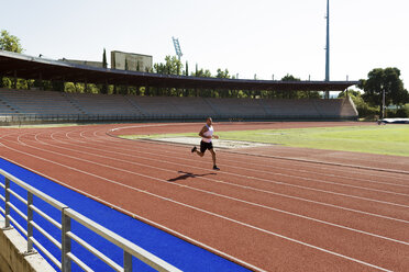 Young sportsman running on tartan track - FMOF000090