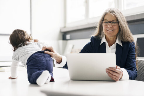 Senior businessswoman sitting at conference table with laptop and baby girl - KNSF000183