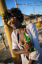 Young woman on the beach relaxing with a bottle of beer - KIJF000674