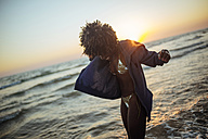 Happy young woman at the seafront at sunset - KIJF000692
