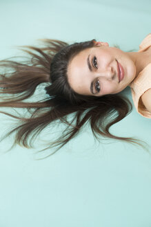 Portrait of smiling brunette young woman lying on floor - TKF000456