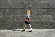Businesswoman holding book and digital tablet walking outdoors - MAUF000682