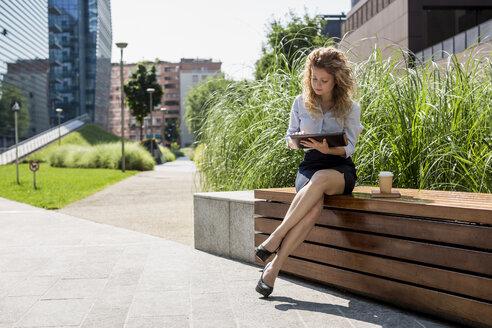 Businesswoman sitting on bench using digital tablet - MAUF000700