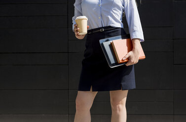 Businesswoman holding coffee to go, book and digital tablet outdoors - MAUF000703