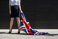 Businesswoman standing outdoors holding British Flag - MAUF000706