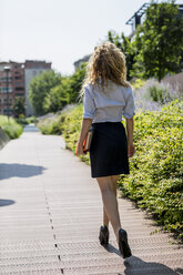 Businesswoman holding book and digital tablet walking outdoors - MAUF000712