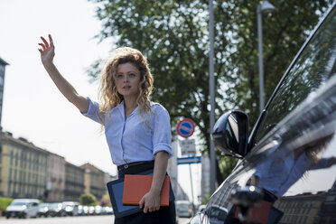 Businesswoman holding book and digital tablet hailing a taxi - MAUF000715