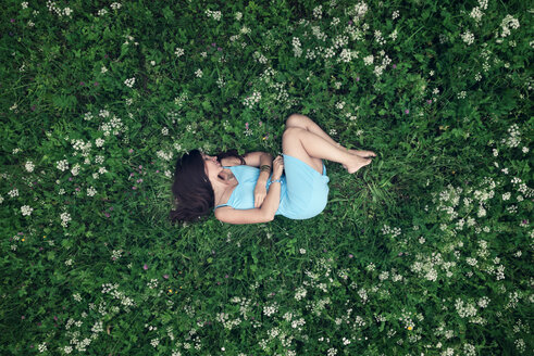 A young woman in a blue dress lying on a summer meadow - MW000107