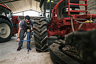 Mechanic changing tractor tyre - JASF001066