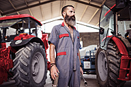 Mechanic in hall with tractors - JASF001072