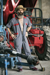 Portrait of confident mechanic with hat at tractor - JASF001078