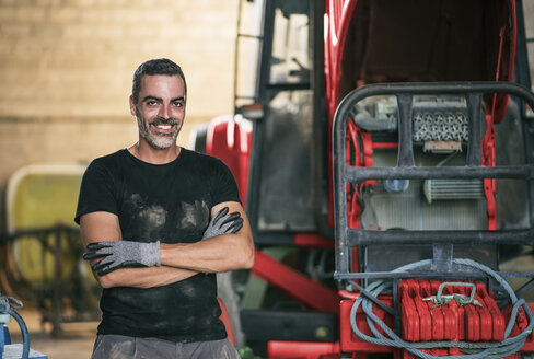 Portrait of smiling mechanic at tractor - JASF001081