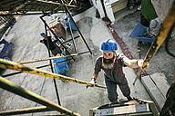 Worker climbing stairs outdoors - JASF001093