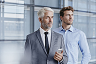 Confident businessman with colleague holding cell phone - RORF000238