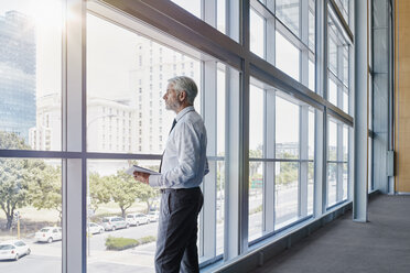 Businessman looking out of a big window - RORF000247