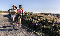 Spain, Asturias, two sportswomen training on the coast, jogging - MGOF002170