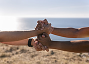 Spain, Asturias, two sportswomen training on the coast, holding hands - MGOF002173