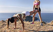 Spain, Asturias, two sportswomen training on the coast, pushup with trainingspartner - MGOF002179